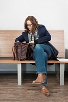 Woman looking in her purse, sitting on a wooden bench in a waiting room