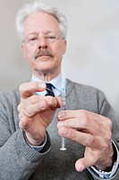 Doctor flicking the air bubbles from a syringe, filled with a drug