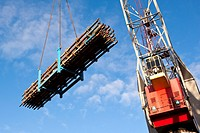 Heavy duty crane lifting a rig with scaffolding materials on a construction yard