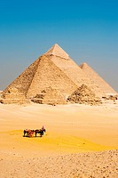 A group of unrecognizable Egyptian tourists dismount their horse cart to view all the pyramids of Giza in a line.