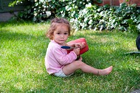 Little girl playing with a watering can in the garden,