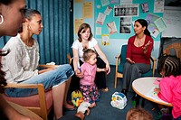 Social worker in discussion group with young mothers and children