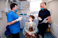 Dentist in consultation with patient, while dental nurse looks on,