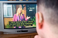 Man with a hearing impairment watching subtitles on television