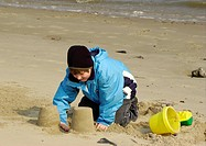 young boy plays on the beach