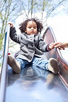 Girl playing on slide in playground