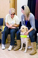 Visually impaired woman with a guide dog talking to a class assistant at NRSB activity day at their centre on Ortzen Street,