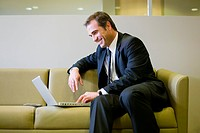 Businessman Using Laptop on Sofa