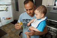 Father and son at home with baby food