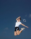 A young woman playing badminton, mid air.