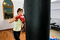 Woman Practicing Boxing with Punching Bag