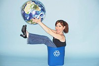 Woman Sitting in Recycling Wastebasket Holding Globe