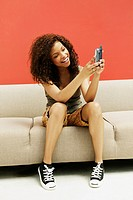 Young Woman Using Cell Phone on Sofa