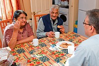 Elderly south Asian parents and son having tea and biscuits