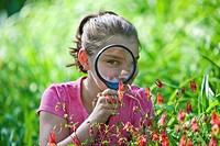 Curious youth using a magnifier to see close-up of flowers
