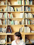 Woman sitting near bookshelves