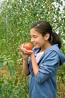 Young girl smelling ripe tomatoes in greenhouse
