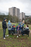 Families chatting by bench with tower blocks behind