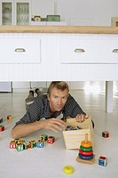 Man picking toys off floor