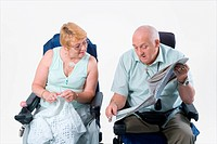 Disabled couple chatting to one another over a newspaper,