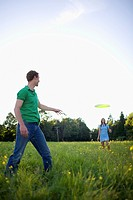 Man and woman playing with flying disk