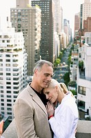 Couple standing on balcony in city