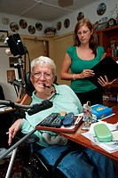 Woman with Cerebral Palsy with mouth_operated computer remote control system which operates door, television, lights etc, with Social Worker