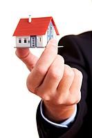Hand hält kleines Haus zwischen den Fingern