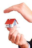 Hand bildet schützend ein Dach über einem kleinen Wohnhaus
