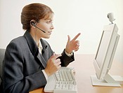 Businesswoman Wearing Headset and Videoconferencing