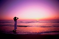 Woman Watching Sunset Over Ocean