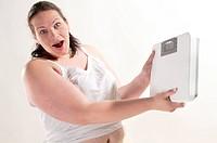 Übergewichtige Erwachsenen Frau mit langen schwarzen Haaren in heller Unterwäsche steht auf der Waage und ist entsetzt über ihr Gewicht, vor weißem Hi...