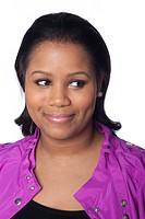 Studio portrait of young African American woman smiling and looking off camera on white background