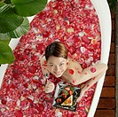 Woman with Dessert in Rose Petal Bath