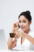 Businesswoman Using Cell Phone, Holding A Credit Card