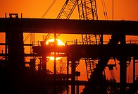 The sun rises behind a crane at a building construction site.