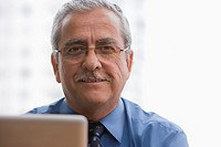 Smiling Hispanic businessman using laptop