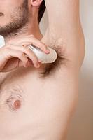 uomo applica deodorante sotto le ascelle