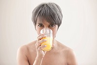 Mixed race woman drinking orange juice