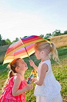 Caucasian girls in field with umbrella
