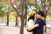 Couple Kissing In A Park In Autumn