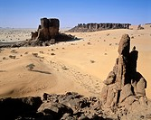 Rock formation at Ennedi desert wilderness, climber overlooking a very remote region of central Sahara, Chad.