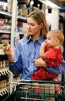 Woman choosing baby food for her daughter at supermarket