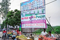 Market with fruit and advertisement for modern housing estate, Agra, Uttar Pradesh, India