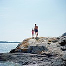 Father and daughter standing on rock by sea, rear view