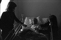 Woman and Girl Visiting Elderly Man in Hospital