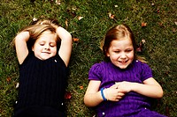 Two Young Girls Laying on Grass