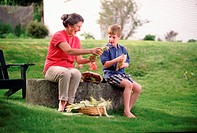 Boy husking corn with grandmother