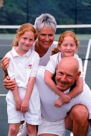 Twin girls with grandparents on tennis court