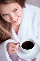 A young girl holding a cup of coffee close up